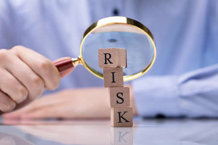 Close-up Of Wooden Blocks With Risk Word In Front Of Businesspersons Hand Holding Magnifying Glass Reklamní fotografie