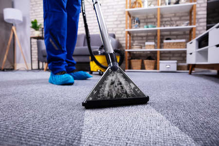 Human Cleaning Carpet In The Living Room Using Vacuum Cleaner At Home Stock Photo