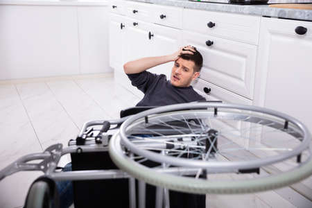 Handicapped Man Fallen Out Of His Wheelchair On Floor In Kitchen