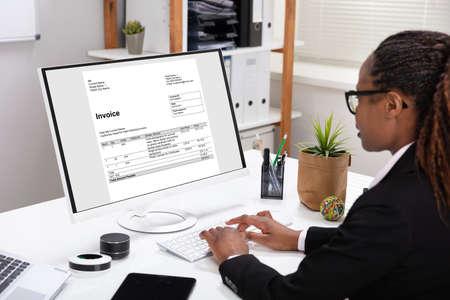 Close-up de la mano de una empresaria comprobando la factura en el portátil sobre el escritorio blanco