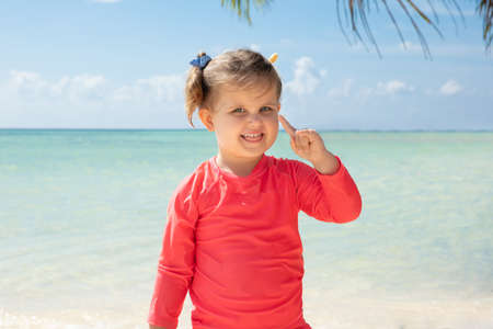 Portrait Of A Smiling Girl Looking At Camera Pointing Her Finger Upward At Beach