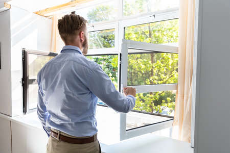 Rear View Of A Man Opening Window To Get Fresh Air At Home Stock Photo