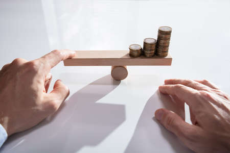 Close-up Of A Businesspersons Hand Balancing Stacked Coins On Wooden Seesaw With Finger Over Desk