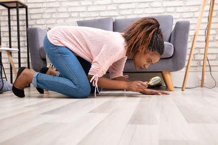 Vista lateral de una mujer joven mirando el piso de madera a través de una lupa