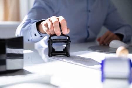 Close-up de la mano de una persona estampada con sello aprobado en el documento en el escritorio