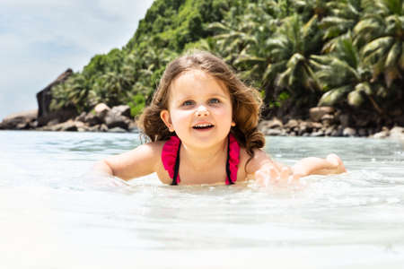 Portrait Of A Smiling Cute Girl Playing In The Sea Water At Beach