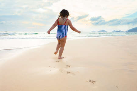 Little Girl In Bikini Running On The Idyllic Sandy Beach Near The Coast