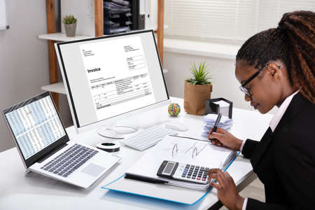 Side View Of Young Businesswoman Calculating Invoice On Computer Screen Near Laptop Standard-Bild