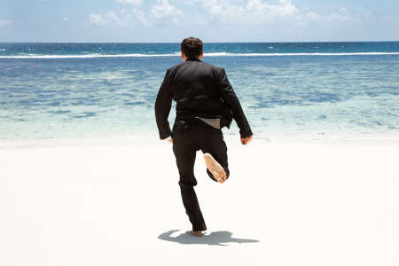 Rear View Of A Man In Black Suit Running Barefoot Toward The Sea At Beach Stockfoto