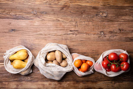 An Overhead View Of Vegetable And Fruits In Net Bag Over Wooden Desk