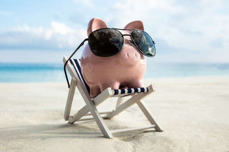 Pink Piggy Bank Wearing Sunglasses Kept On The Deck Chair At Beach Stockfoto