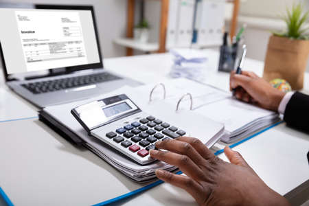 Close-up Of A Businesswoman Calculating Invoice Using Calculator Near Laptop Stockfoto