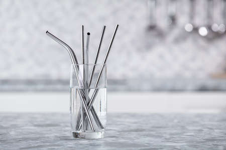 Metal Straws In Transparent Glass Of Water On Kitchen Worktop Stockfoto