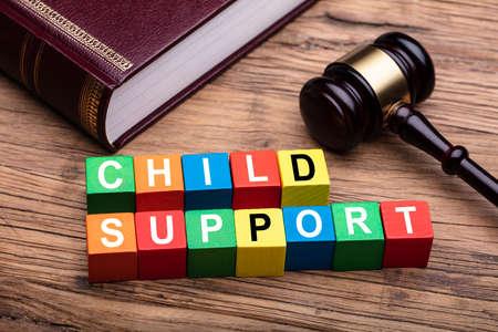 Wsparcie dla dzieci Kolorowy blok z Biblią i młotkiem nad drewnianym biurkiem w sali sądowej