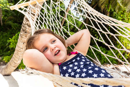 Close-up Of A Cute Little Girl Relaxing On Hammock At Beach Stock Photo