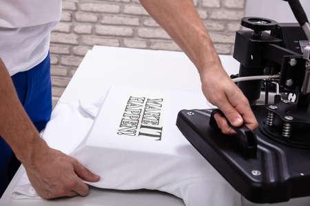 Hombre imprimiendo en camiseta en taller Foto de archivo