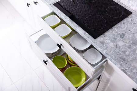 Set Of Different Clean Plates Inside The Opened Drawers In Kitchen