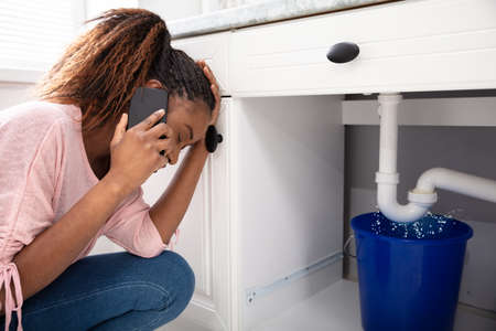 Young Woman Calling Plumber Crouching In Front Of Water Leaking From Sink Pipe