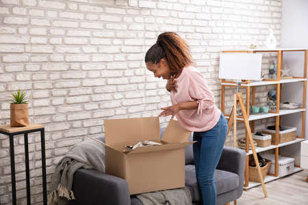 Happy Woman Opening The Parcel Box At Home