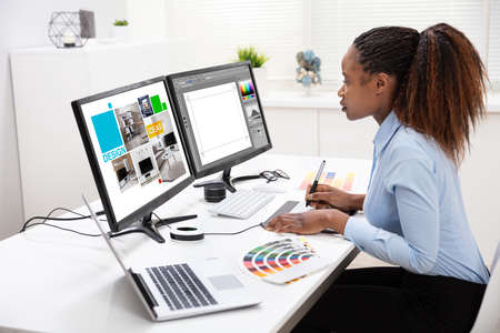 Young Female Designer Editing Photos On Computer In Office Banco de Imagens - 122929175