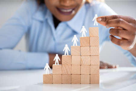 Close-up Of White Human Figures Leading On Top Of Wooden Blocks In Office Banque d'images - 122929178