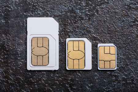 Three Types Of Sim Cards Arranged In A Row Over Concrete Gray Background