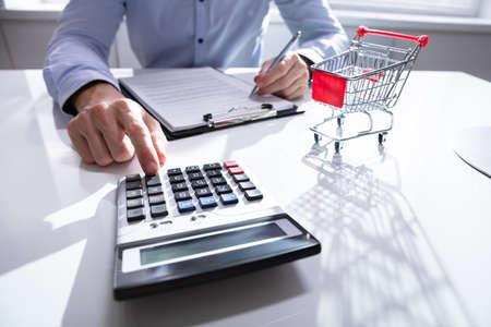 쇼핑 트롤리 근처에서 쇼핑 비용을 계산하는 남자의 근접 스톡 콘텐츠