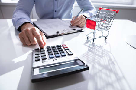 Close-up Of Man Calculating Shopping Expenses Near Shopping Trolley Reklamní fotografie