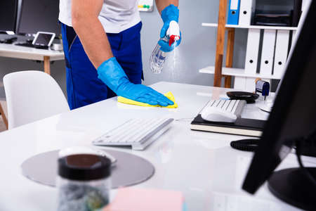 Conserje limpieza escritorio blanco en la oficina moderna
