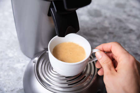 Close-up Of Persons Hand Holding Coffee Cup Under Coffee Maker Over Kitchen Counter
