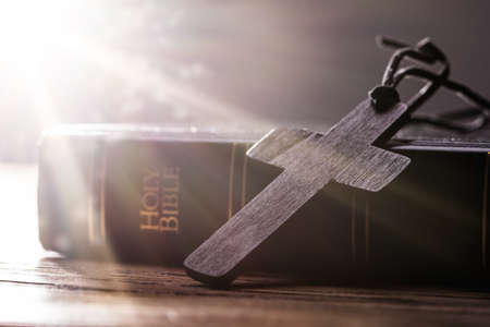 Wooden Christian Cross On Holy Bible Over Wooden Table Stockfoto