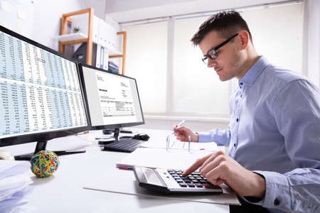 Side View Of Businessman's Hand Calculating Invoice At Workplace