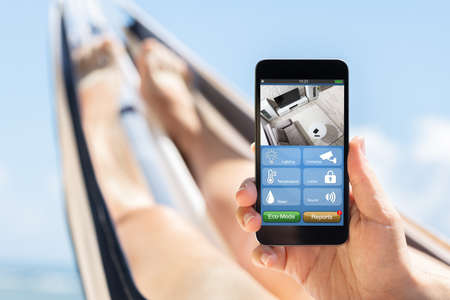 Close-up Of A Woman Lying On Hammock Holding Mobile Phone With Apps On Smart Home Imagens