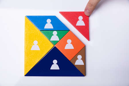 Businessmans Hand Building Tangram Square Block With Human Figures