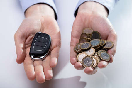 An Elevated View Of Mans Hand Holding Black Car Key And Golden Coins Stockfoto