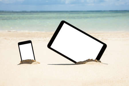 Mobile Phone And Digital Tablet Dig On Sandy Beach Near The Idyllic Sea