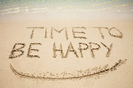 Close-up Of Time To Be Happy Text And Smile Written On Sand At Beach