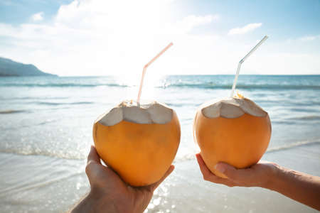 Close-up Of Couples Hand Holding Coconut With Drinking Straw In Front Of Idyllic Sea Stockfoto