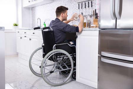 Joven discapacitado sentado en una silla de ruedas preparando la comida en la cocina