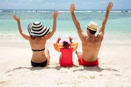 Rückansicht einer Familie, die ihre Hände hebt und am Strand sitzt und den Urlaub genießt?