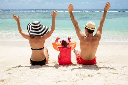 Rear View Of A Family Rising Their Hands Sitting On Beach Enjoying The Vacation