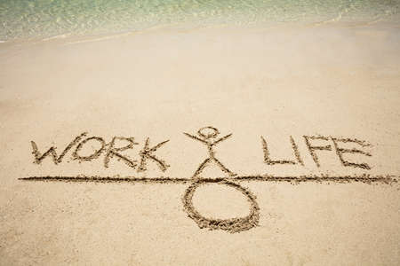 Close-up Of Work And Life Balance Concept On Sand At Beach