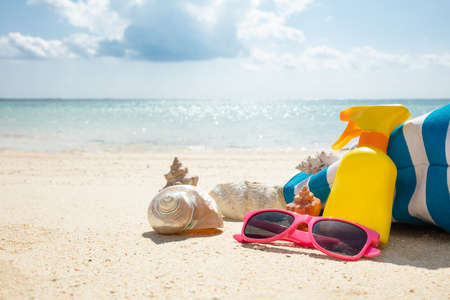 Sunglasses, Seashell, Sunscreen Lotion And Handbag On Beach