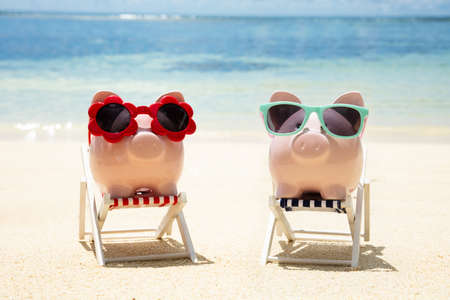 Close-up Of Two Pink Piggybanks With Different Type Of Sunglasses On Deck Chair At Beach