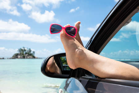Close-up Of Sunglasses Over The Womans Feet Out Of Car Window Against Blue Sky