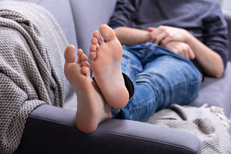 Close-up Of Man Relaxing On Sofa With His Legs Crossed In Home 스톡 콘텐츠