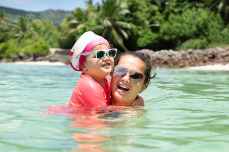 Close-up Of Mother And Daughter Wearing Sunglasses Swimming In The Sea