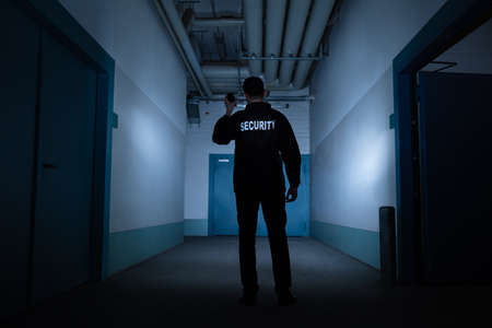 Rear View Of A Male Security Guard With Flashlight Standing In Corridor Stockfoto