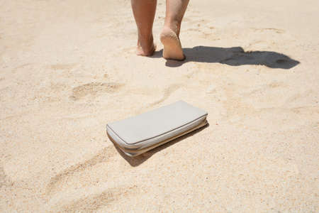 Close-up Of A Woman Lost A Purse With Money On The Sandy Beach Stockfoto