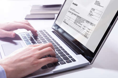 Close-up Of A Businessmans Hand Checking Invoice On Laptop Stockfoto
